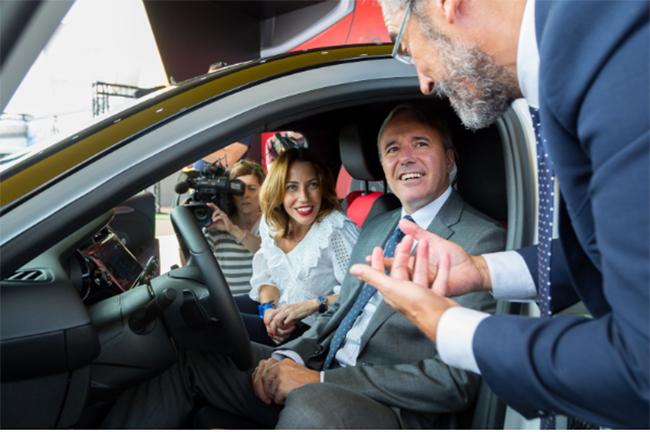 José Antonio León, director de Comunicación del Grupo PSA, muestra al alcalde y a la concejala el Corsa eléctrico que se fabricará en Zaragoza.